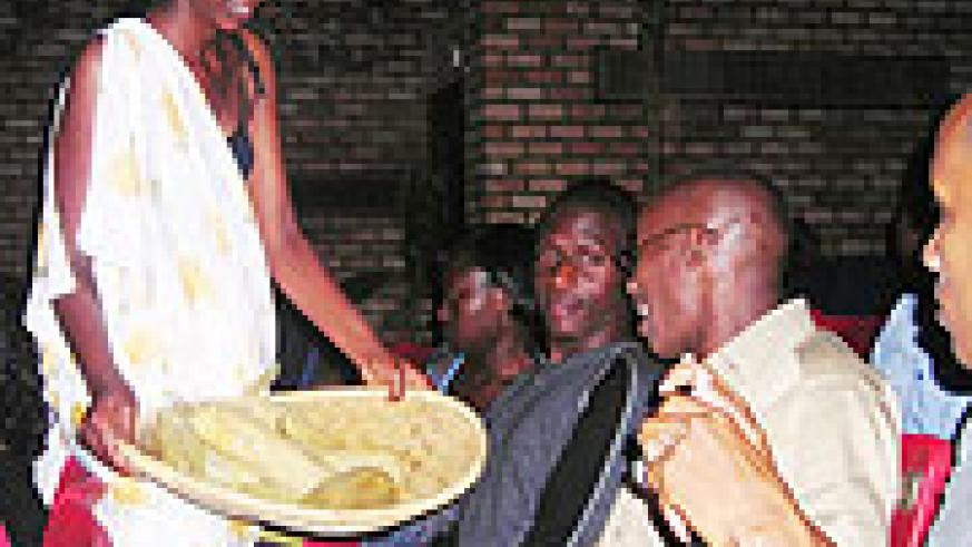 Sharing the harvest_ Show goers served Maize during the celebration of Umuganura by the NUR traditional ballet group. (Photo by, P. Ntambara)