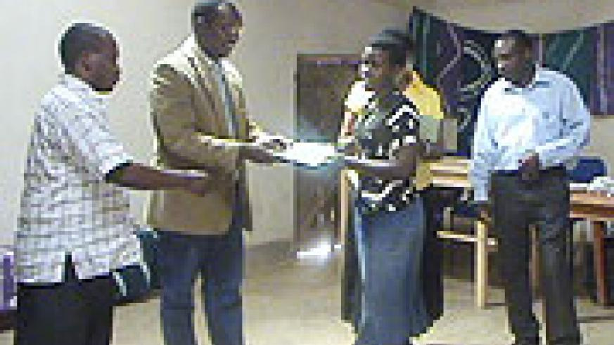 A participant receives a certificate of merit from UNHCR National Health Coordinator Dr Augustin Gatera (Photo S Nkurunziza)