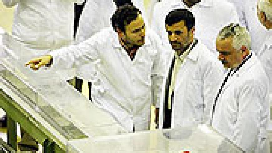Iranian President Mahmoud Ahmadinejad, center, listens to a technician in a nuclear fuel manufacturing plant in Isfahan, Iran