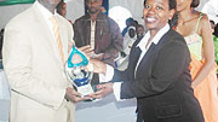 Rwandatel's CEO, Patrick Kariningufu receiving a trophy from the Trade and Industry Minister, Monique Nsanzabaganwa after emerging best overall exhibitor. (Photo J Mbanda).