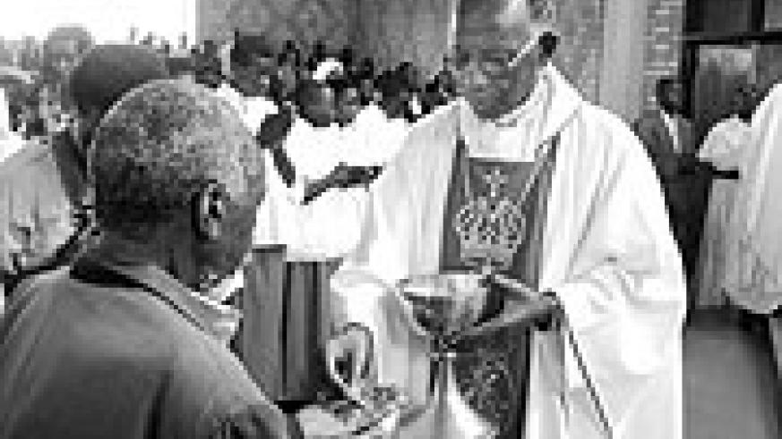 Retired Bishop  Fredrick Rubwijanga giving Holy Eucharist to Christians.