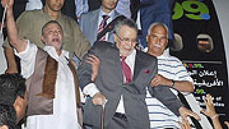 Libyan Abdel Baset al-Megrahi, who was found guilty of the 1988 Lockerbie bombing, center, is helped down the airplane steps on his arrival at an airport in Tripoli, Libya