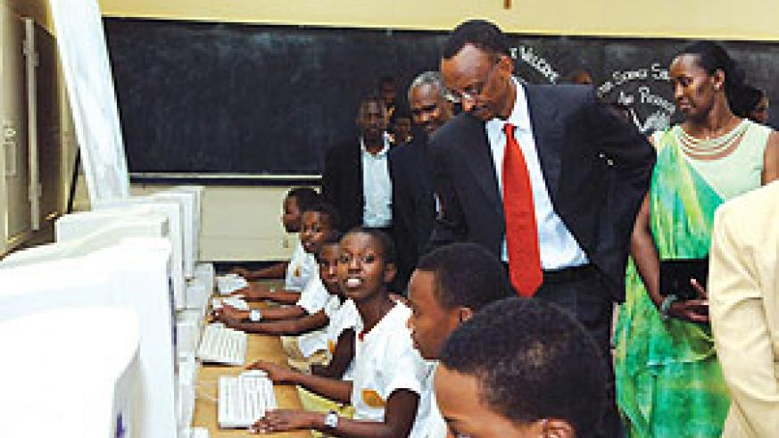 President Paul Kagame inspects Groupe Scolaire Notre Dame de Karubanda students as they work in the computer lab. On his left is First Lady Jeannette Kagame who was honoured by the school for her role in promoting the girl child's education.(Photo/U.V)