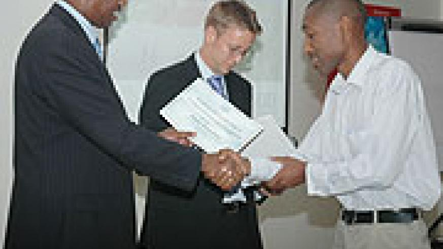 Youth Minister Protais Mitali hands a certificate to an ALCP graduand at the event .(Photo F Goodman)