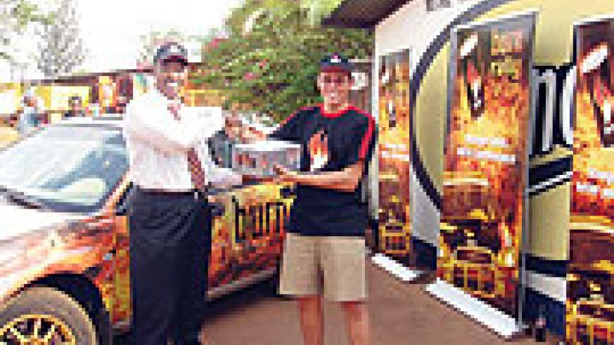 Olivier Costa receives a cartoon of Burn energy drink from Bralirwa's marketing manager Freddy Nyangezi.