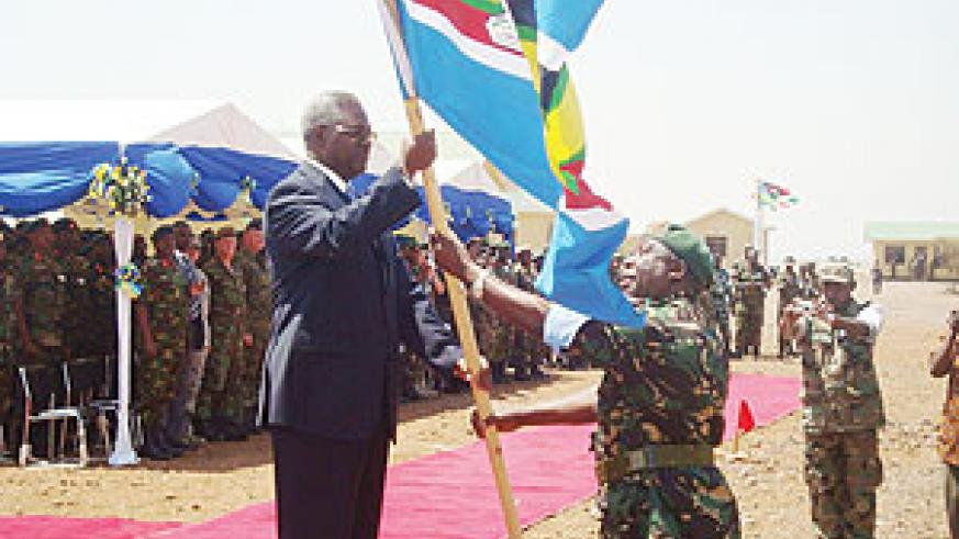 The Minister of Defence, Gen Marcel Gatsinzi, receiving the East African flag yesterday at Monduli, Tanzania (Photo/ G. Muramira)