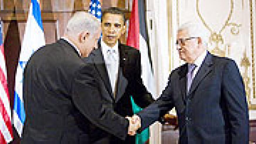 U.S. President Barack Obama looks on as Israeli Prime Minister Benjamin Netanyahu  and Palestinian President Mahmoud Abbas shake hands before a trilateral meeting at the Waldorf-Astoria in New York.