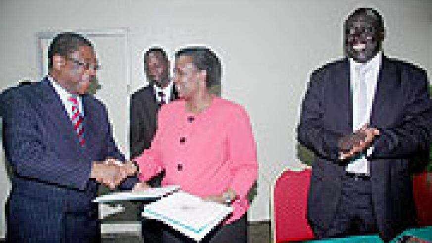 Foreign Affairs Minister Rosemary Museminali (C) and Kenyan Attorney General Amos Wako shake hands after signing as justice Minister Tharcise Karugarama looks on. (Photo J. Mbanda)