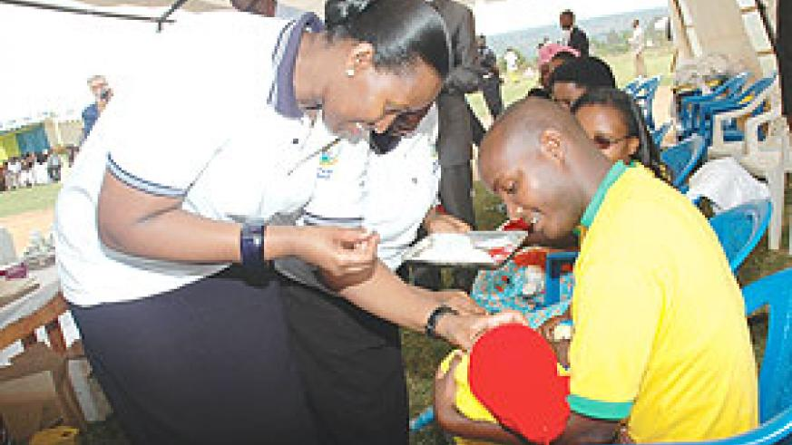 First Lady Jeannette Kagame administering a dose of Vitamin A to a child in Gashora as she launched the Immunisation Program yesterday. (Photo J Mbanda)