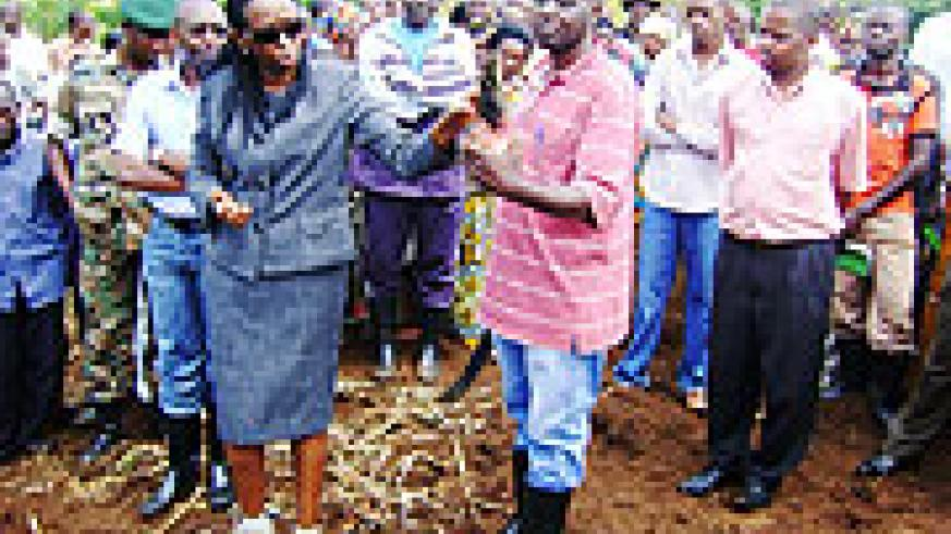 Minister of Agriculture, Dr. Agnes Kalibata examines a banana sucker. This was during her tour of Rwamagana yesterday. She advised farmers on proper methods of banana growing.(Photo/ S. Rwembeho)