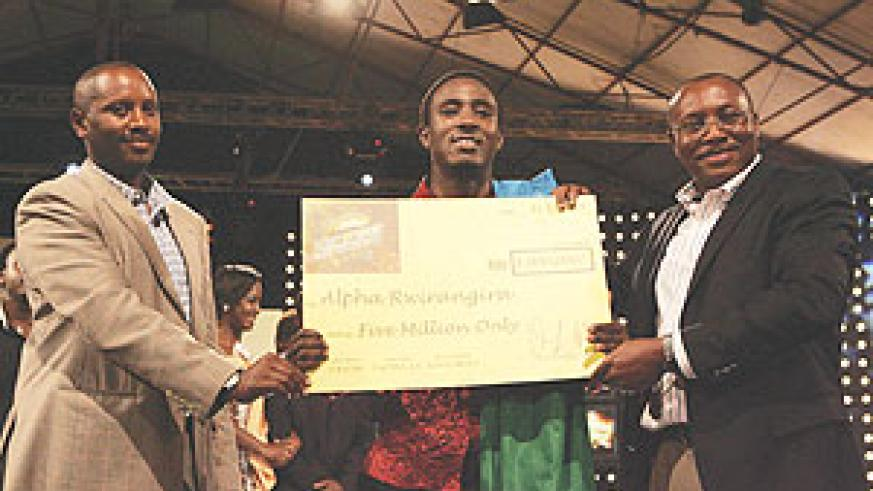 Rwanda's envoy to Kenya William Kayonga (left) joins East Africa Breweries  Limited Group Managing Director Mr Seni Adetu (right) in presenting the Tusker Project Fame 3 Winners Kshs 5 million dummy cheque to Rwanda's Alpha