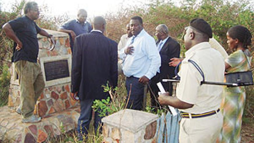 Everready Nkya, (in black T-shirt), a Tanzanian national who buried the Genocide remains, takes a team of CNLG officials around the burial site in Ngara district, Tanzania. (Courtesy photo).