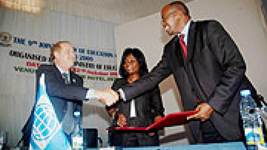 Finance Minister James Musoni shaking hands with DFID's Richard Arden as World Bank Country Manager Mimi Ladipo looks on after the signing. (Photo/ J. Mbanda)