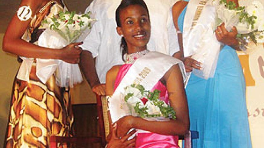 State Minister for Minerals and Natural Resources, Vincent Karega, stands behind Miss East Africa Rwandan chapter 2009 Cynthia Akazuba seated, Annet Mahoro (left) 1st runner-up and the 2nd runner-up. (Courtesy Photo)