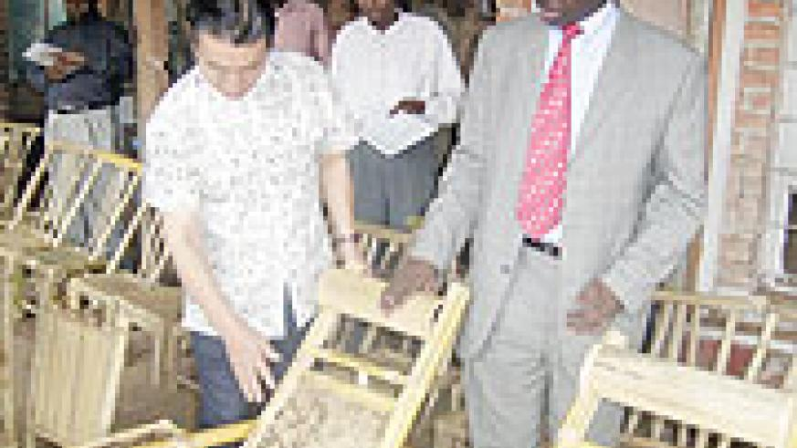 Chinese Economic expert, Wang Qin shows Hon. Stanislas Kamanzi some of the products.