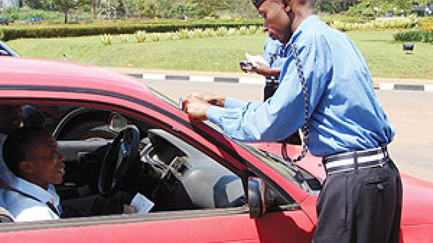 A Police officer puts a sticker on a car during the Road safety week.