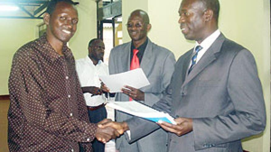 Minister Murekezi hands a certificate to Joshua Mugisha, one of the trained retrenched civil servants. (Photo / D. Sabiiti)
