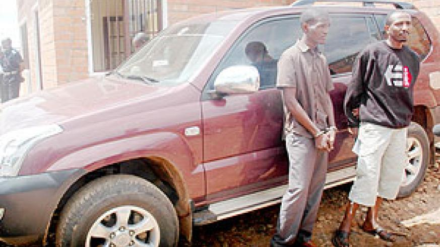 NABBED! Nsengimana (handcuffed) and Rurangwa in front of the recovered stolen car. (Photo;J. Mbanda)