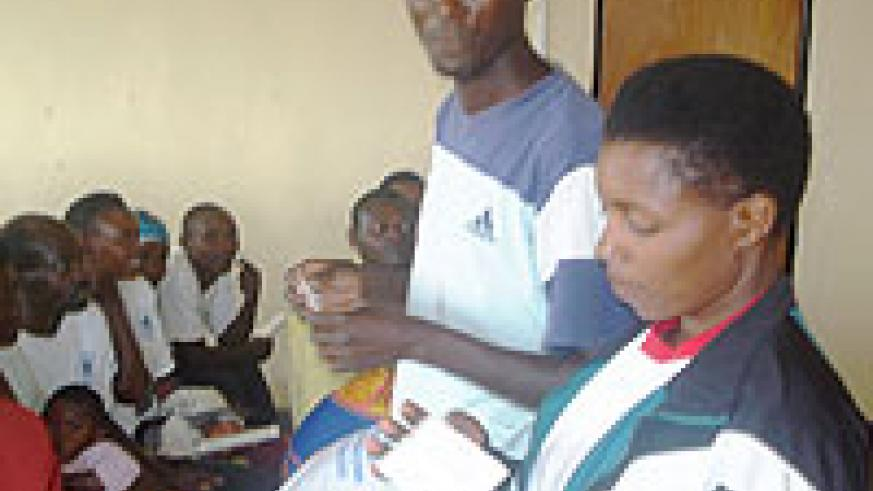 Two local leaders demonstrating how to use condoms.