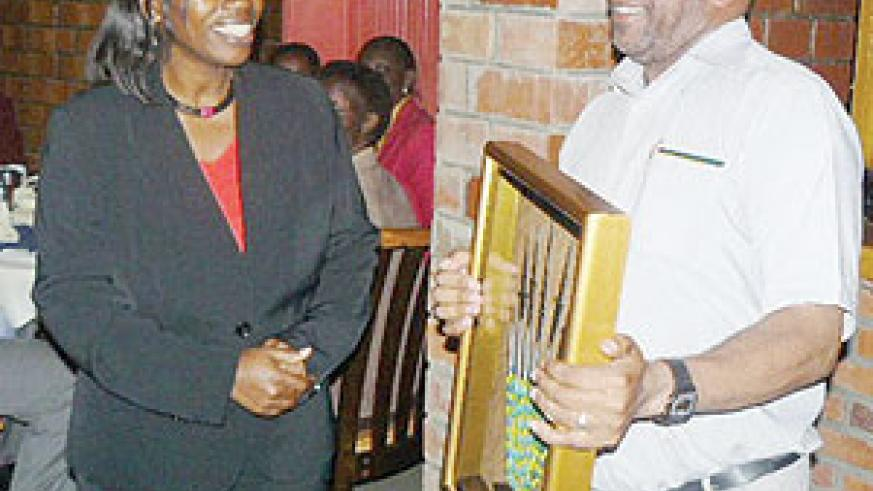 Vincent Sebahire receiving the best performing award from Monique Nsanzabaganwa minister of trade and industry