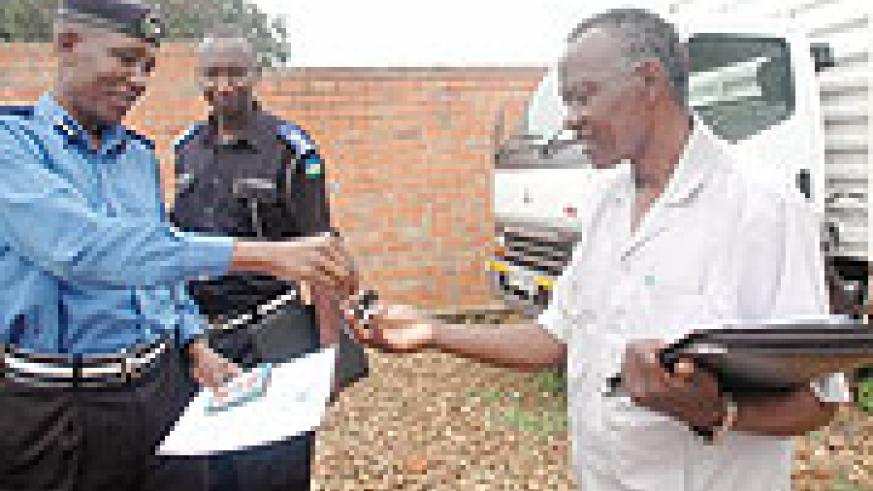 Tony Kuramba of the national police hands over the keys of the recovered vehicle to his Kenyan counterpart, Simon Ondego