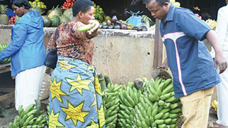 A man buys Bananas in Kimironko market. Restaurant owners around Kimironko have complained of the hiking of foodstuff prices at the market.