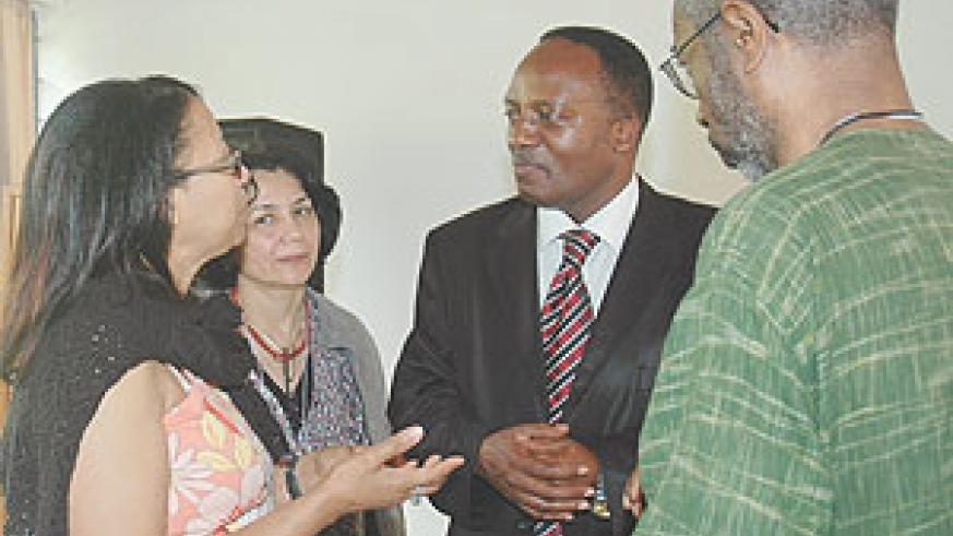 The Executive Secretary of the National Unity and Reconciliation commission Jean Baptiste Habyarimana (C) listens to some participants who attended the conference.
