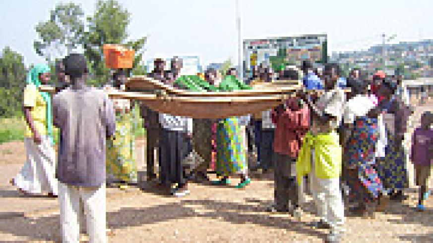 One of those injured in the clash being transported to Byumba hospital in a traditional stretcher. (Photo: A. Gahene)