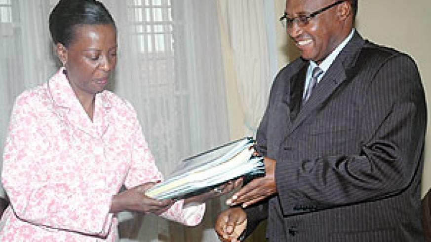 Foreign Affairs Minister Louise Mushikiwabo (L) hands over ministry documents to the Minister of Cabinet Affairs yesterday. (Photo/ J. Mbanda)