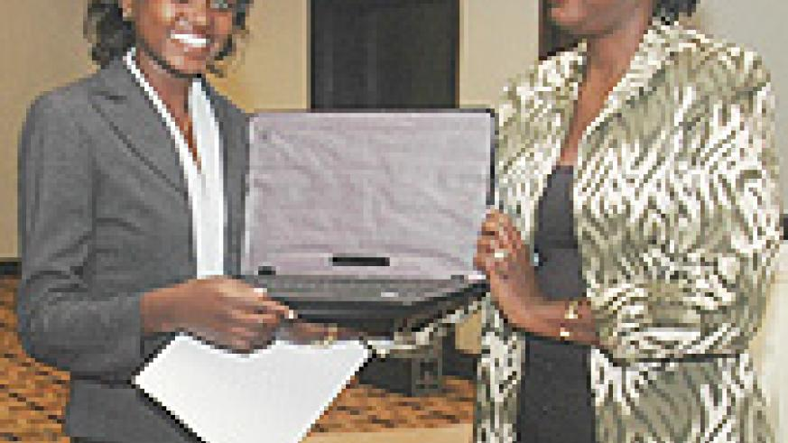 The New Times' Irene V. Nambi receiving her award from Denise Mupfasoni of Access Project yesterday (Photo/ F. Goodman)