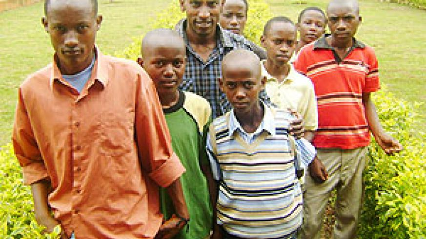 Headmaster  John Africa (centre) poses for a photo with some of his pupils who execelled in PLE. (Photo: S. Rwembeho)