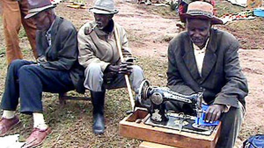 Jonas Rwabukwisi working on his sewing machine in company of fellow old men (photo S Nkurunziza)