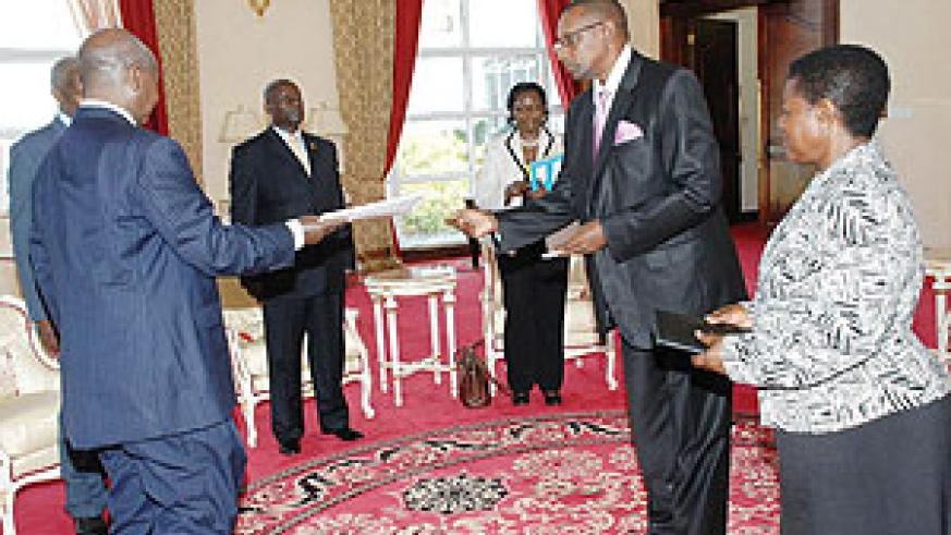 Rwanda's new High Commissioner to Uganda, Frank Mugambage (R), presenting his credentials to President Yoweri Museveni on Tuesday.