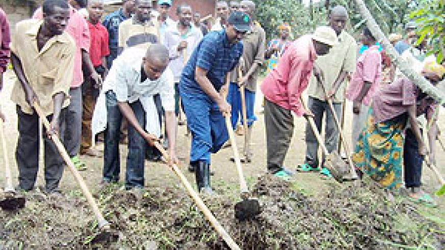 LEADING BY EXAMPLE: Karongi Mayor Bernard Kayumba (centre) leading residents in the community work to fix the Karongi-Rubavu road. (Photo: S. Nkurunziza)