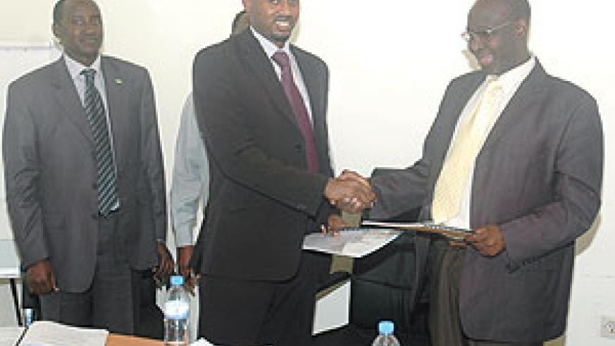 Outgoing MHC Board Chairman, Venuste Karambizi, hands over instruments of power to his successor, Arthur Asiimwe, yesterday (Photo FGoodman)