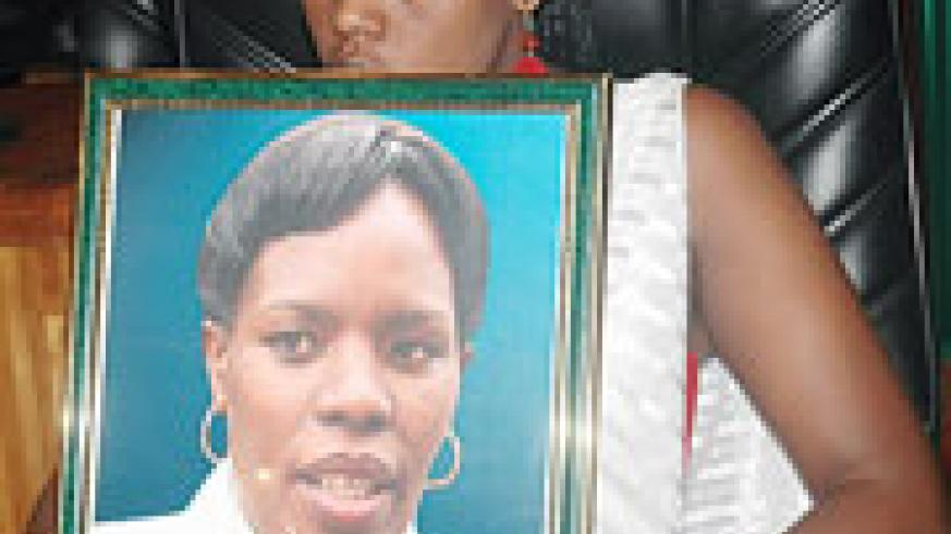 One of the late Kanakuze's daughters holding her  portrait yesterday. (Photo J Mbanda)