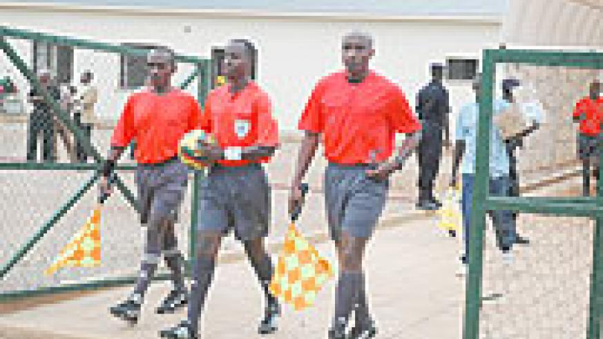 JOB WELL DONE: Hudu Munyemana (C), Celestin Ntagungira (R)and Eric Ruhamiriza (L) take to the field to officiate a local league match between Rayon Sport and Atraco. (File photo)