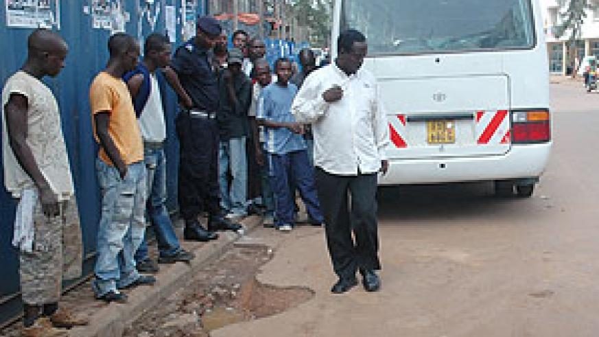 The aftermath of the grenade attack. Onlookers at the sight of the Rubangura attack, Police Spokesman, Supt Eric Kayiranga (left).
