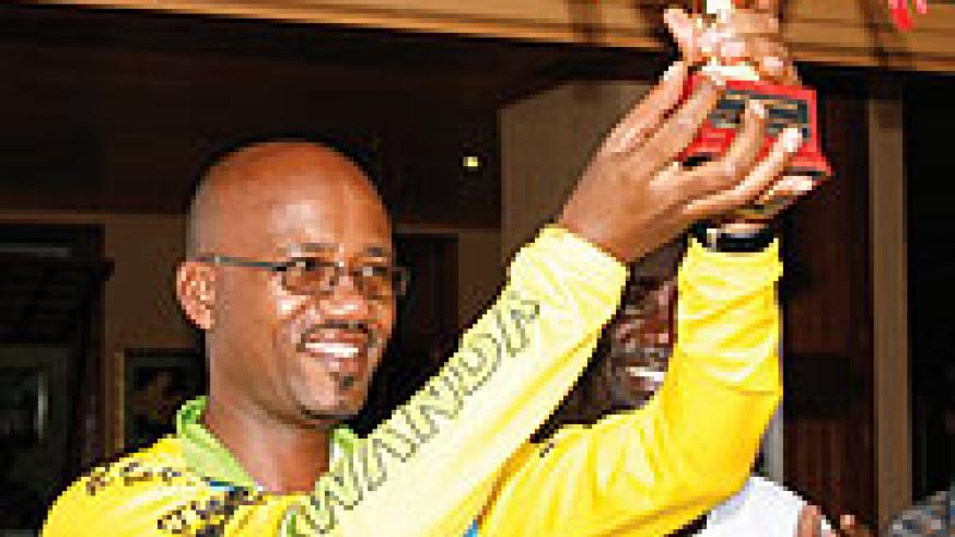 President of the national cycling federation Aimable Bayingana shows off Team Rwanda's trophy on Sunday.