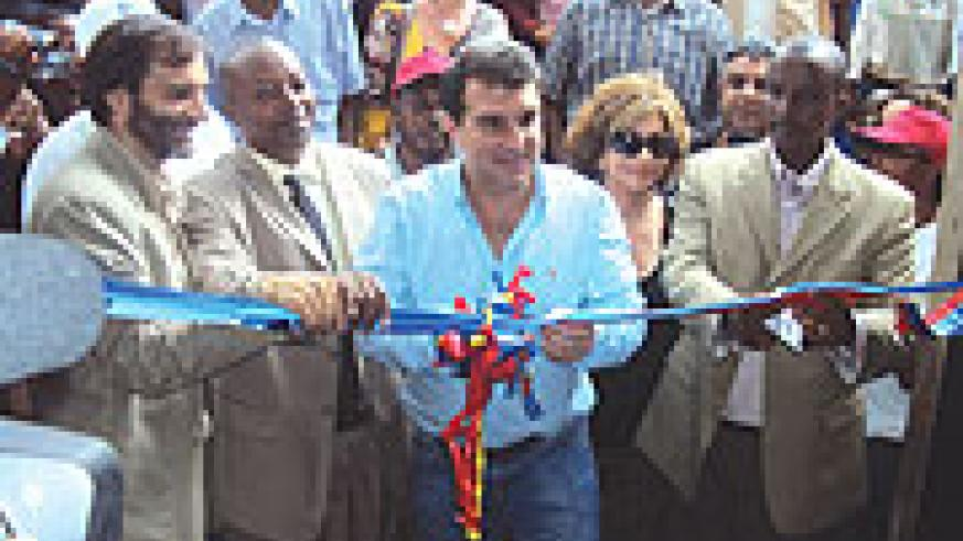 FC Barcelona President Joan Laporta and other officials cutting a ribbon at the opening of a multi-purpose hall at Kixiba camp yesterday. (Photo/ S. Nkurunziza)