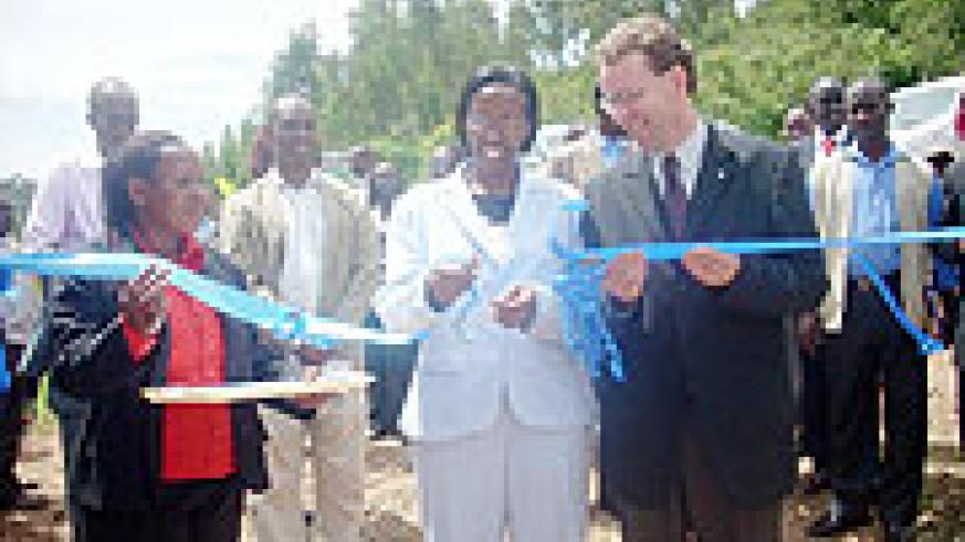 Minister Coletha Ruhamya (C) cuts the tape during the inauguration of a water project in Huye. (Photo: J.C Gakwaya)