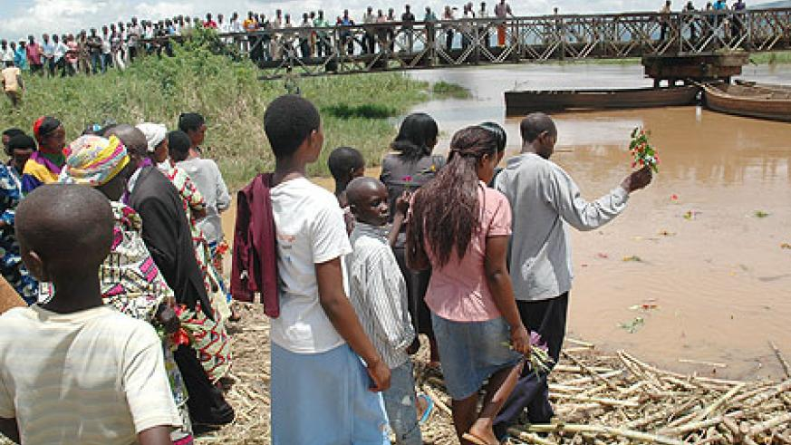 Relatives and friends of victims who were dumped into River Nyabarongo throwing flowers into the river (photo J. Mbanda)