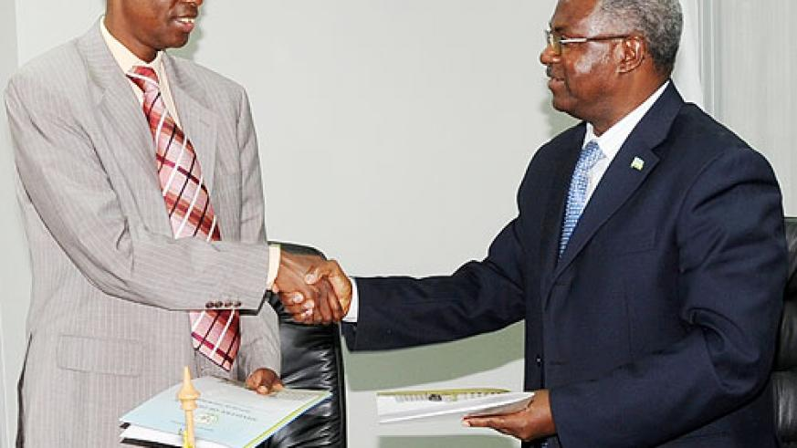 Defence Minister Gen. James Kabarebe (L), and the Minister of Disaster preparedness and Refugees, Gen. Marcel Gatsinzi, shake hands at the handover yesterday. (Photo J Mbanda)