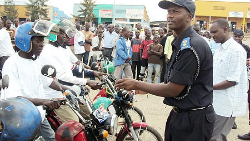 Supt. Désiré Tuyizere placing a sticker on motorists in Gitarama. (Photo: D. Sabiiti)