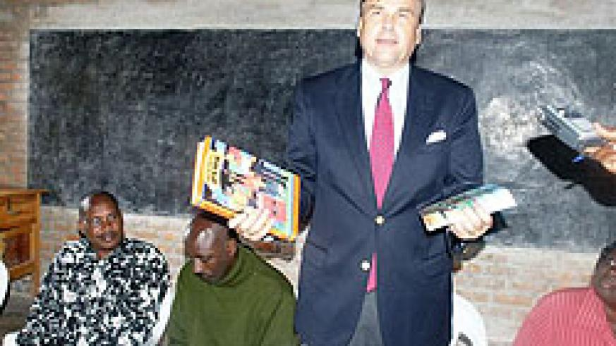 Ambassador Stuart Symington displays some of the books donated to the school yesterday. (Courtesy Photo)