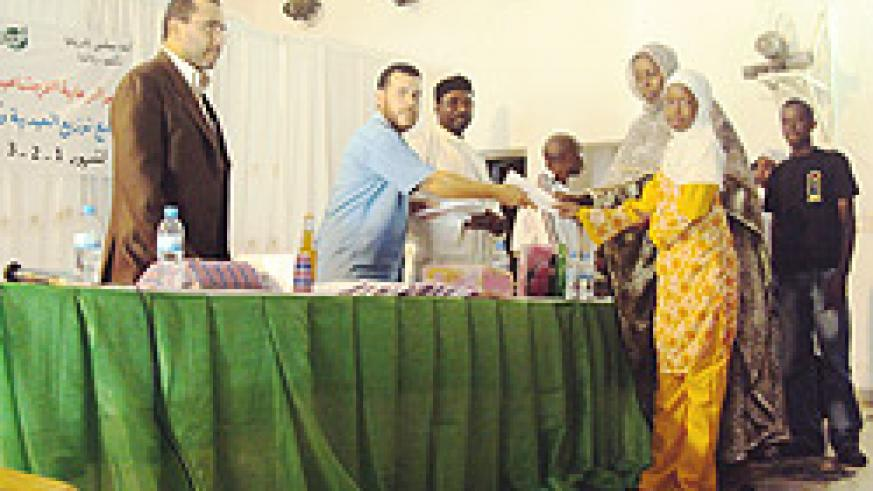 Muhamoud Abudalazim handing over an envelope and scholastic materials to one of the beneficiaries yesterday. (Photo / F. Ndoli)