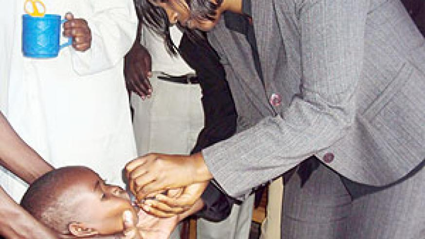 Simbi Dative Mukabaliza, Karongi district vice Mayor in charge of Social Affairs administers a vaccine  to one of the children. (Photo: S. Nkurunziza)