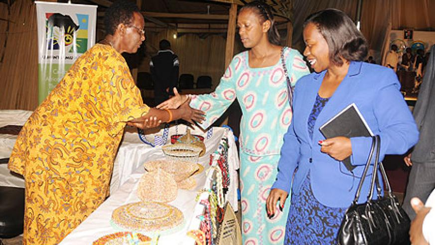 The Minister of Commerce, Monique Nsanzabaganwa and Jeanne d'Arc Gakuba (M) talking to an exhibitor at Rwanda Village yesterday. (Photo; B. Asiimwe)