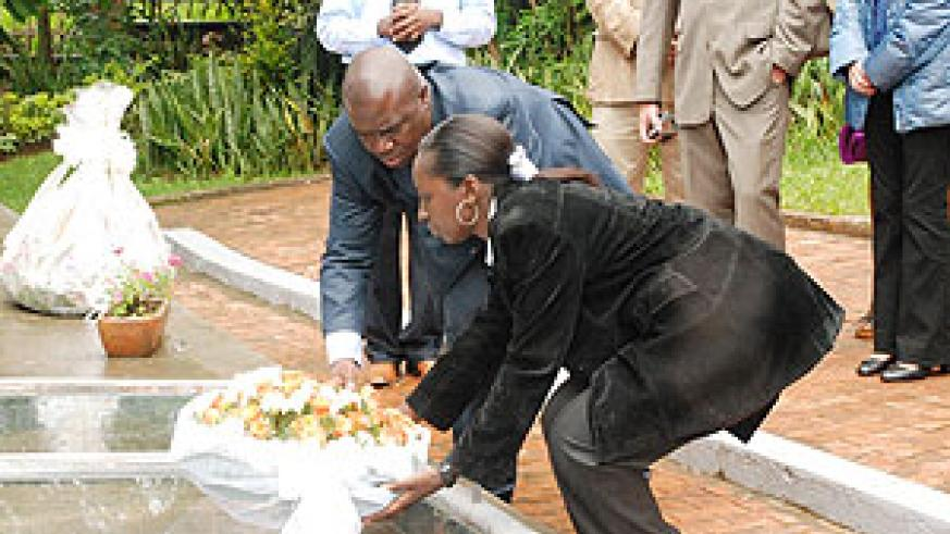 RGC's CEO Philip Brizoua (L) laying flowers on a mass grave at Kigali Memorial Centre, Gisozi. (Photo; S. Butera)