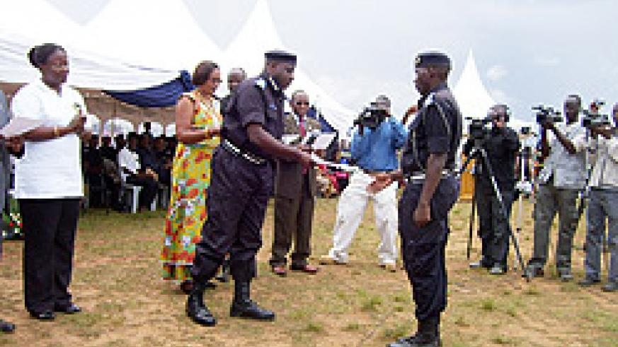 The Commissioner General of Police, Emmanuel Gasana handing over a certificate to a policeman who completed a course in fighting GBV yesterday. (Photo; A.Gahene)